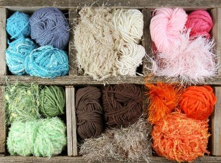gomitoli di lana: tante palline filati colorati in una scatola di legno invecchiato