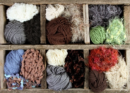 gomitoli di lana: molti autunno palle filati colorati in una scatola di legno invecchiato