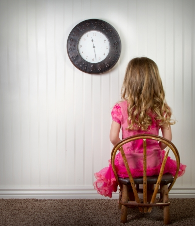 naughty girl: A young child in time out or in trouble, with clock on wall