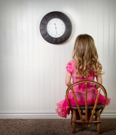 disciplina: Un niño pequeño en el tiempo de espera o en problemas, con el reloj en la pared