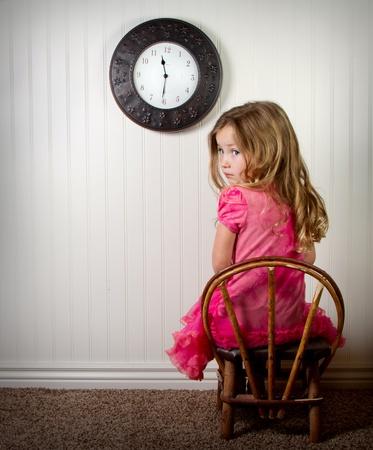 kleines Mädchen in time out oder in Schwierigkeiten suchen, mit Uhr an der Wand Standard-Bild