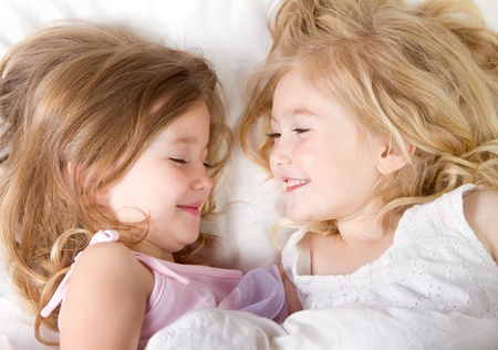 Preschool age girls in bed having a sleep-over photo