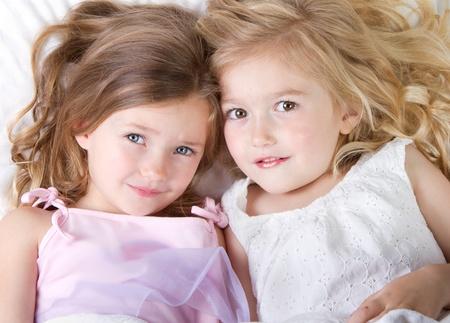 Voorschoolse leeftijd meisjes in bed te slapen dan het opzoeken van Stockfoto