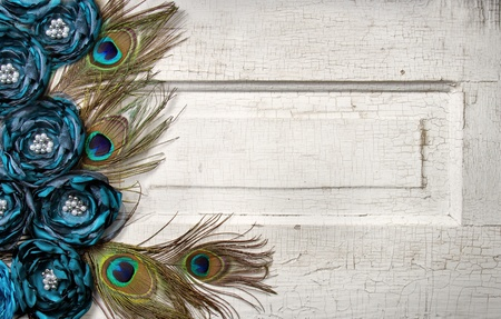 Peacock feathers and flowers on a white antique or vintage door for background Foto de archivo
