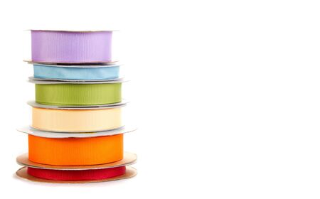 spools of ribbon in rainbow colors stacked on white background photo