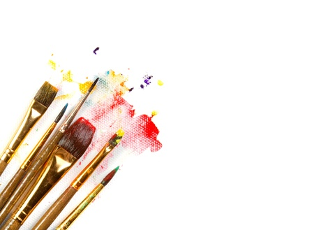 art and craft equipment: Surtido de pinceles de pintura en el fondo del lienzo con salpicaduras de pintura sobre fondo blanco