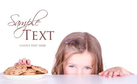 A cute young girl stealing a cookie from a plate photo