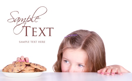 Cute girls steals cookies from a plate isolated on white Banco de Imagens