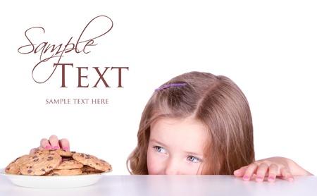 robando: Muchachas lindas roba cookies de una placa aislada en blanco