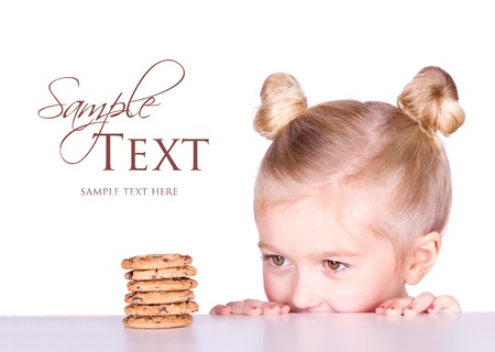 little girl looking at a pile of cookies on a counter or table isolated on white background Foto de archivo