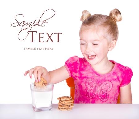 schattig klein meisje dunken cookie in melk op een witte achtergrond