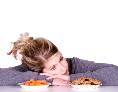 Woman on diet making eating choices, chosing between carrots or cookies.