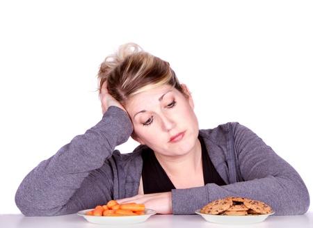 dieting: Vrouw op dieet het maken van het eten van keuzes, kiezen van tussen de wortelen of cookies.