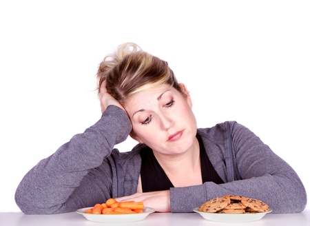 dieting: Woman on diet making eating choices, chosing between carrots or cookies.