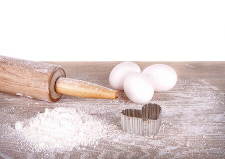 Baking still life, flour, eggs and rolling pin on an isolated white background photo