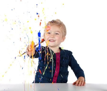 Little girl painting paint splatters on a window, isolated on white Foto de archivo