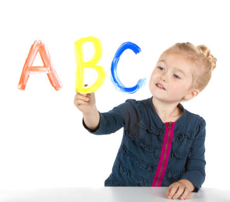 abc's: Little girl paints ABCs or letters on window, isolated on white Stock Photo