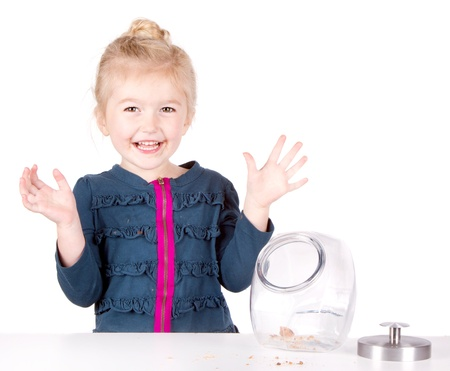 Mischievous girl steals cookies from cookie jar, isolated on white background photo