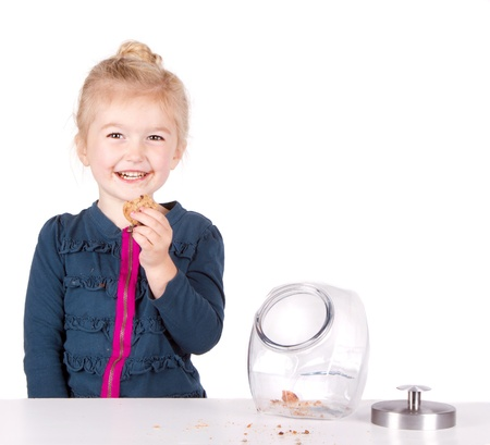 Girl stealing cookie out of cookie jar isolated on white background photo