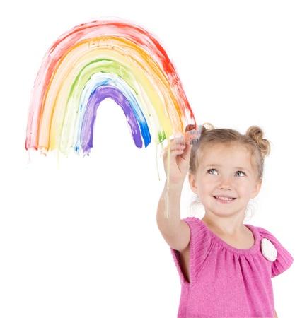 Little girl painting rainbow on window isolated on white photo