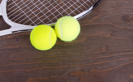 Tennis balls and tennis racket still life wooden background photo