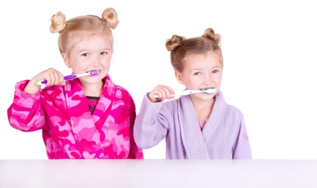Two cute girls brushing their teeth in bathrobes isolated in white photo