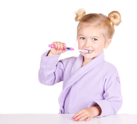 Cute little girl brushing teeth in bathrobe isolated on white Archivio Fotografico