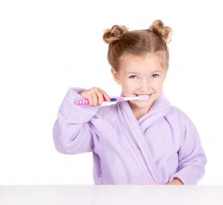Cute little girl brushing teeth in bathrobe isolated on white Banque d'images