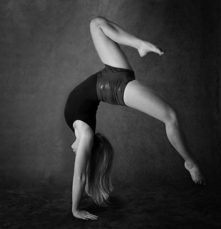 Girl doing back bend or gymnastics in black and white photo
