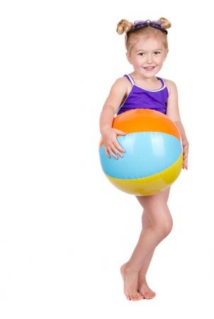 beachwear: Little girl holding beach ball isolated on white