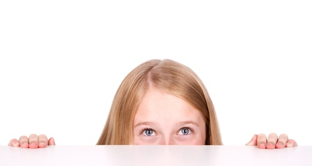 Girl or teen peeking from behind a table isolated on white