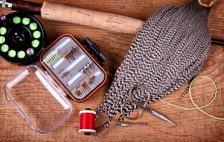 Collection of fly tying and fishing equiptment on a wooden plank