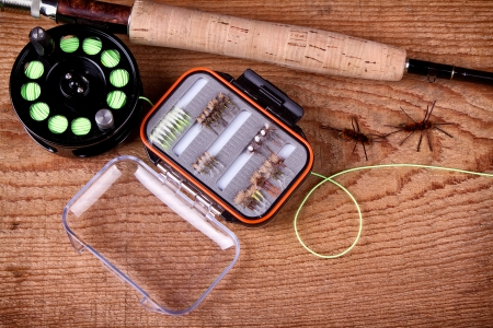 Collection of fly fishing equiptment on a wooden plank photo