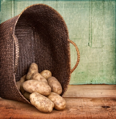russet: Russet potoatoes spilling out of a basket on wooden crate, grunge background Stock Photo