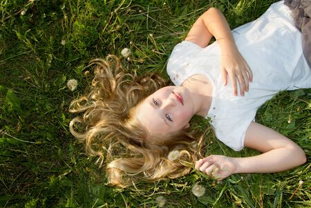 Girl laying in a grassy field with dandelions photo