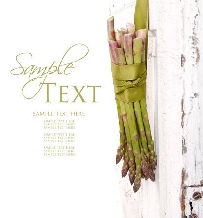 Bunch of asparagus hanging on a vingage or antique doore Foto de archivo