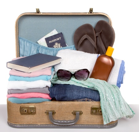 Packed vintage suitcase full of vacation items Standard-Bild