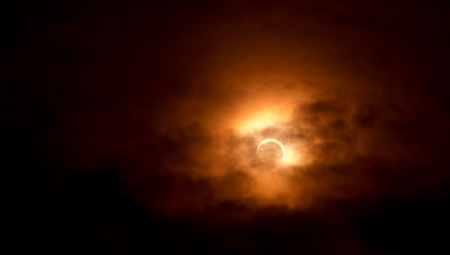 Solar eclipse, photos of moon covering the sun with light cloud cover. May 20, 2012 photo