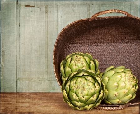 artichokes spilling out of a basket, with a grunge background Banco de Imagens