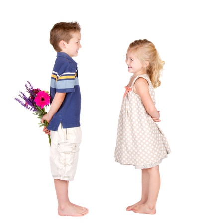 cute little girls: A girl looking at a  boy  with flowers behind his back, valentines day pose  Stock Photo