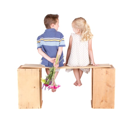 Little girl and boy sitting on a wooden bench holding flowers, isolated on white