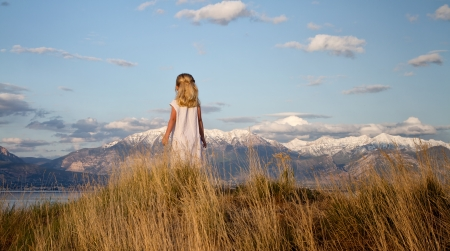 Little girl on a grassy hill looking into a mountain landscape photo