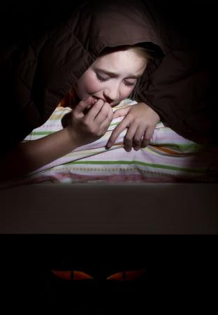 scared child: Chica asustada en su cama durante la noche imaginando monstruos bajo la cama Foto de archivo