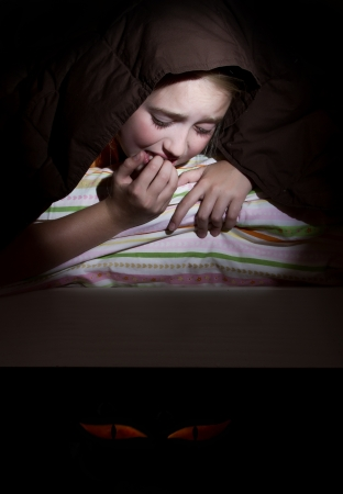 frightened: Girl scared in her bed at nighttime imagining monsters under bed