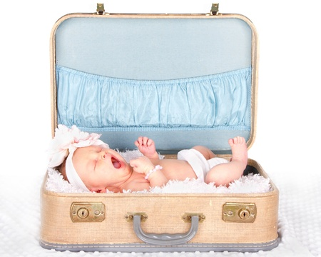 Newborn baby yawning in a vintage suitcase