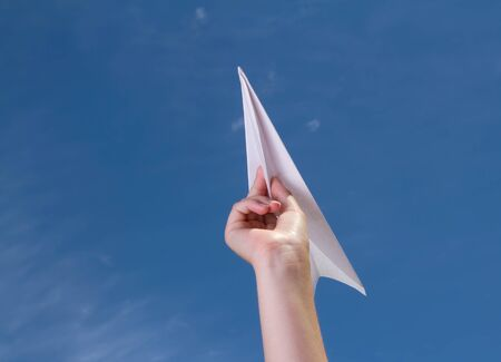 child holding a paper airplane agains a blue sky photo
