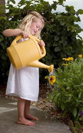 young girl watering flowers with watercan outdoors
