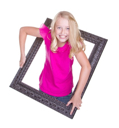 A girl climbing through a picture frame, isolated on white photo