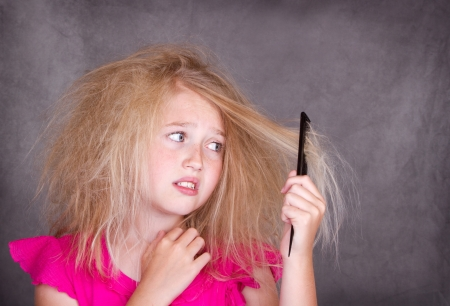 Girl with crazy tangled hair trying to comb it out photo