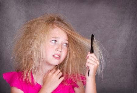 groviglio: Ragazza con i capelli arruffati pazzo cercando di pettine fuori